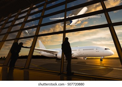 Tourists at the airport. Travelers looking through the window onto the runaway and airplanes. Sunset back light and silhouettes of people.