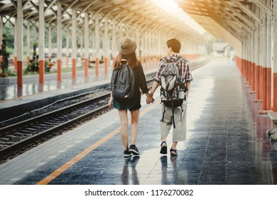 Tourists from Asia, two people are travelling by train.