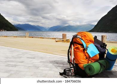 Tourists backpack . Norvegian Fjords on the background