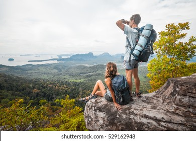 Tourists with backpacks relaxing on top of a mountain and enjoying the view of valley