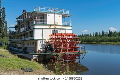 tourists boarding a sternwheel river boat to cruise the Chena River near Fairbanks in Alaska with the river and forest in the background