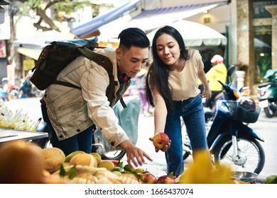 Tourists buying fruit at the street market