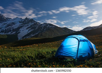 Tourists camp in mountains at night. Hikers tent in night mountain valley. Camping in highlands