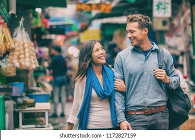 Tourists in Chinatown street market laughing together exploring Asian town. Asia travel adventure, two people walking visiting Hong Kong. Young woman, man in love.