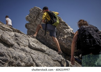 Tourists climb on a rock in order to reach Agia Anna beach in Amorgos island, Greece, on the 7th of August 2013.
