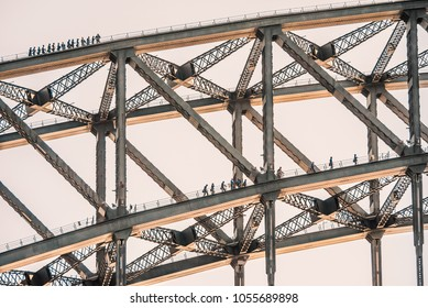 Tourists climb on two layers of the Sydney Harbour Bridge. The sun is catching the bottom of the metal bridge.