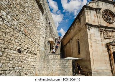 Tourists climb the staircase to the ancient city walls of Dubrovnik near Saint Saviour Church on the Dalmation coast of Croatia on a sunny summer day