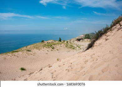 Tourists climbing up and down a popular dune, dune overlooking Sleeping Bear Dunes National Beach. Panorama.