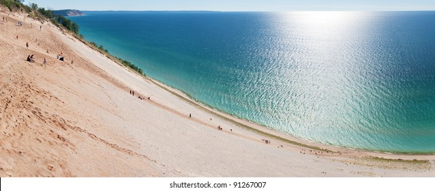 Tourists climbing up and down a popular dune overlook at Sleeping Bear Dunes National Lakeshore. Panorama.