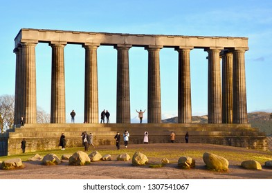 Tourists climbing on the National Monument. a popular tourist attraction, modelled on the Parthenon in Athens that sits on Calton Hill overlooking Edinburgh city. Edinburgh Scotland, UK. fEBRUARY 2019