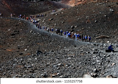 Tourists climbing the Santorini volcano, forming a winding pattern against the black basalt from the last eruption in 1950