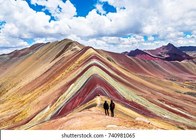 Tourists couple stand and look afar at Rainbow Mountains, Cusco, Peru