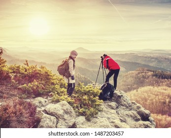 Tourists couple stay on summit and takes memory picture with camera on tripod.  Hiker and photo enthusiast stay with tripod on cliff and thinking. Dreamy fogy landscape