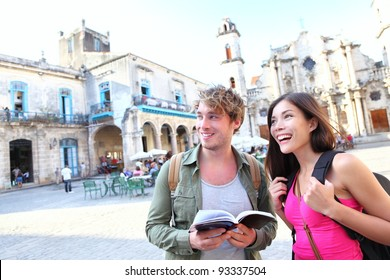 Tourists couple travel in Havana, Cuba having fun. Young multiracial happy couple on backpacking vaction standing on Plaza de la Catedral, Old Havana.