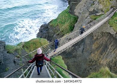 Tourists cross Carrick-a-rede Rope Bridge, popular tourist attraction in Northern Ireland. Ballintoy, County Antrim, Northern Ireland 18.11.2019
