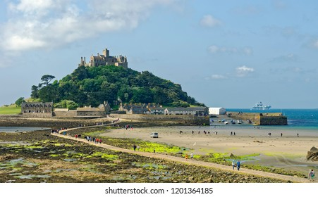 Tourists crossing over the exposed causeway at low tide between the tidal island of St. Michael's Mount and Marazion, Cornwall, England