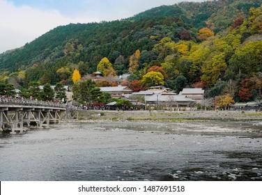 Tourists crossing the Togetsukyo Bridge over Katsura River at Arashiyama in autumn season, colorful trees on mountain ,japanese village shop in front at ARASHIYAMA,Kyoto, Japan.