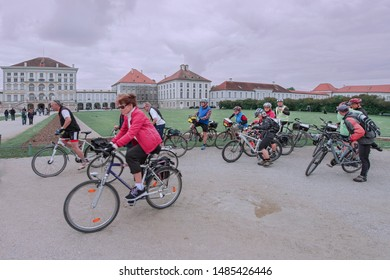 Tourists and cyclists at The Nymphenburg Palace, designed by Agostino Barelli in 1664. Their rooms show their original baroque decoration and neoclassical style. Munich. German. 05/2014.