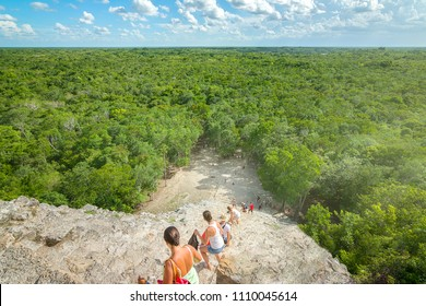 Tourists descending amazing Nohoch Mul pyramid in Coba, Quintana Roo, Mexico