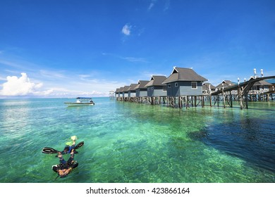 Tourists do water rescue in diving training course with dramatic view of crystal clear water and coral in blue sky background at Mabul Island , Sabah, Malaysia