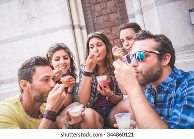 Tourists eating slush, talking and looking each other