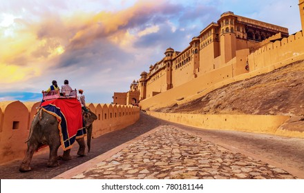Tourists enjoy an elephant ride at Amer Fort Jaipur Rajasthan at sunset.