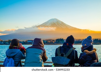 Tourists enjoy freely view Mt.Fuji Beautiful sunset from the pleasure boat on the water are wonderful of Lake Kawaguchiko in winter , Japan