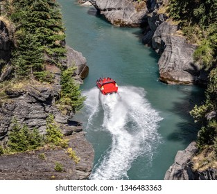 Tourists enjoy a high-speed boat ride on Shotover river near Queenstown. Queenstown is a recognized center of extreme entertainment. South Island of New Zealand