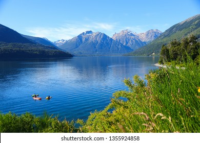Tourists enjoying the blue waters of Mascardi lake in a canoe, south of San Carlos de Bariloche in Patagonia, Argentina, under a snow-covered mountain of the Andes.
