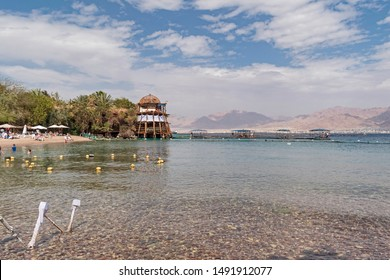 tourists enjoying dolphin reef beach in eilat in israel with akaba jordan in the background