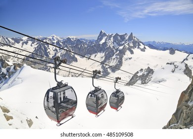 Tourists enjoying the majestic landscape in gondolas from Point Helbronner to Aiguille du Midi, France