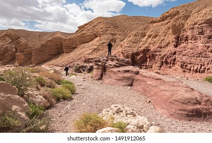 tourists enjoying the red sandstone boulders on a hike in the red canyon near eilat in israel