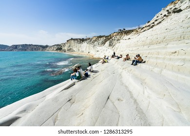 Tourists enjoying the sun and sea sitting on the white cliffs at Scala dei Turchi (Stair of the Turks). Realmonte, Agrigento province, Sicily, Italy, May 2018