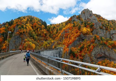 Tourists enjoying vibrant fall colors on the rocky cliffs by Hoheikyo Dam, a reservoir in a beautiful gorge under environmental protection in Shikotsu-Toya National Park in Sapporo, Hokkaido, Japan