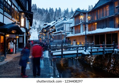 Tourists enjoying the view of Ginzan Onsen, a famous hot spring town in Obanazawa, Yamagata, Japan, with bridges over a stream flanked by traditional Ryokan & buildings on a cold snowy winter evening