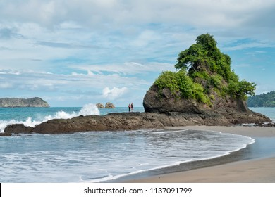 tourists enjoying the view and ocean waves on top of a rock at Antonio Manuel park, Costa Rica