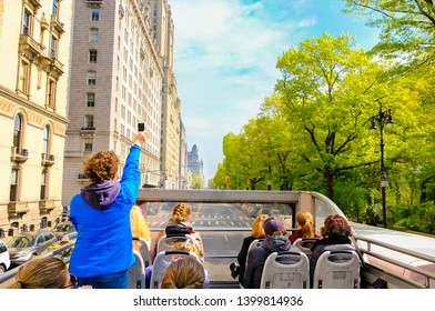 Tourists enjoying views of New York City from top of open roof bus in spring; woman in blue is taking photos with her smartphone