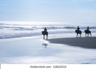 tourists exploring kuta beach bali at sunset on horseback