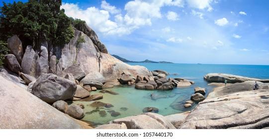 tourists exploring the rocksy coastline and clear sea pools near the grandfather rock on lamai beach on ko samui island in the guld of thailand