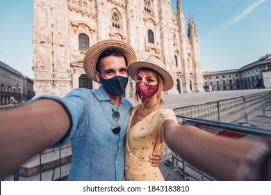 Tourists with face mask taking a selfie at Duomo of Milan, Italy. New normal lifestyle concept with couple visiting Milano. - Shutterstock ID 1843183810