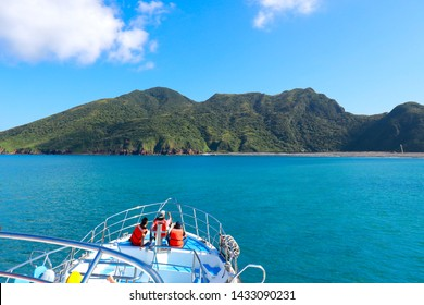 Tourists' finger point to the island and sit on the front deck of the tour ferry that is heading to the island for vacation. The concept of leisure, adventure, discovery, tourism or new life style.