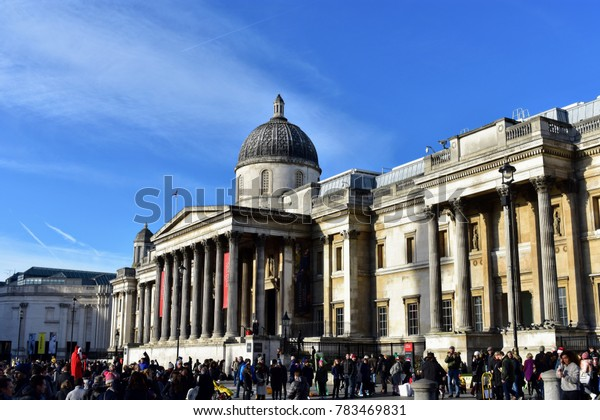 Tourists in front of the National Gallery on a sunny day, Trafalgar Square, London, December 2017.