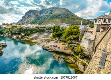 Tourists gather along the bank of the Neretva River below the old Mostar Bridge in Mostar Bosnia in anticipation of a high dive.