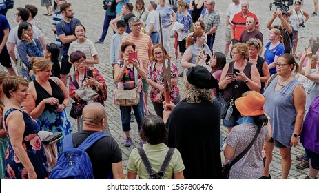 Tourists gather around the famous night watchman of Rothenburg Germany while he gives a talk on the medieval times in this beautiful walled village.  August 2019.
