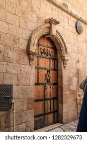 Tourists gather near door of Station VI of the Via Dolorosa in Old City Jerusalem, Israel