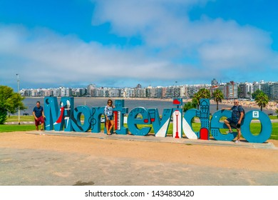 Tourists getting their picture taken in front of the famous Montevideo sign on the Ramblas, Montevideo, Uruguay, January 27th 2019