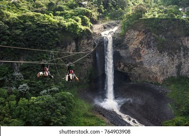 Tourists gliding on the zip line trip against Bridal veil (Manto de la novia), waterfall in Cascades route, Banos, Ecuador