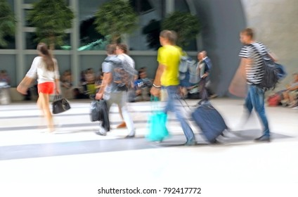 Tourists go to the station with baggage, blurred image