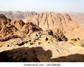 Tourists hiking in Mount Sinai,  a mountain in the Sinai Peninsula of Egypt, for its famous sunset and sunrise scenery. Mount Sinai is considered a holy site by the Abrahamic religions.