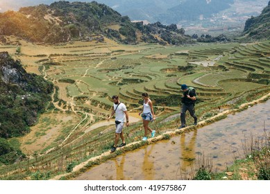 Tourists hiking in the mountains with backpack near rice terraces in Sapa, Vietnam. Reflaction of people at puddy fields during the walking tour.